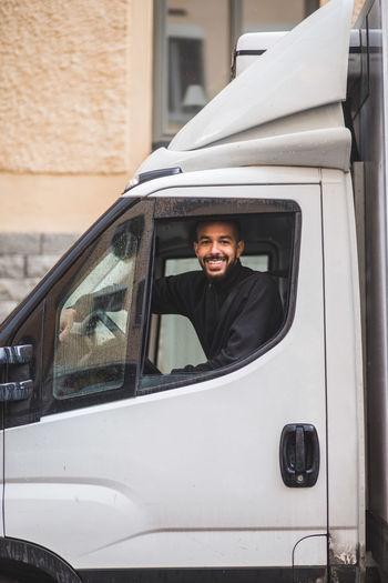 Portrait of smiling man sitting in car