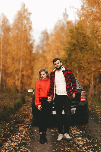 A romantic couple in love in warm sweaters is walking traveling by car in the autumn forest in fall