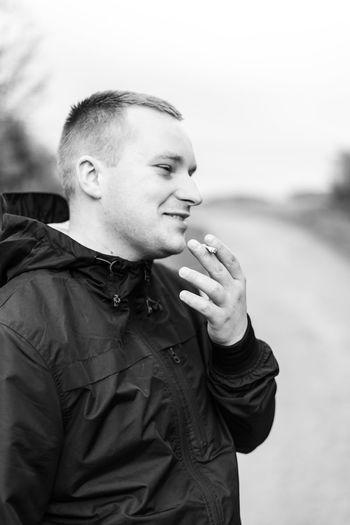 Smiling man smoking cigarette against sky