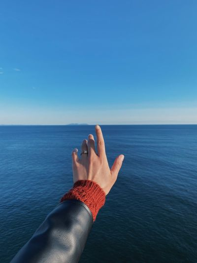 Close-up of hand gesturing against sea against clear blue sky