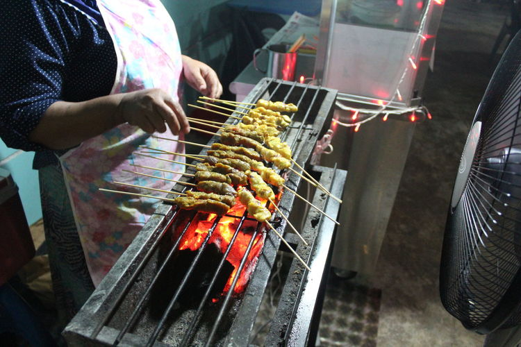 Midsection Of Woman Preparing Meat On Barbecue Grill