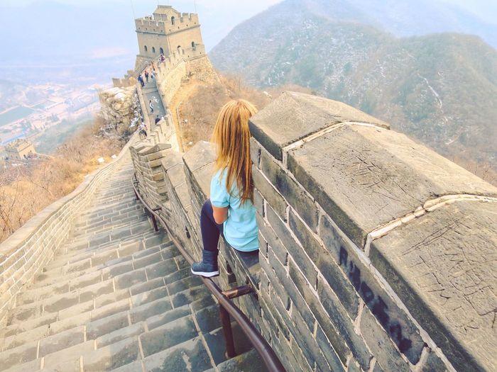 Rear view of woman sitting at great wall of china