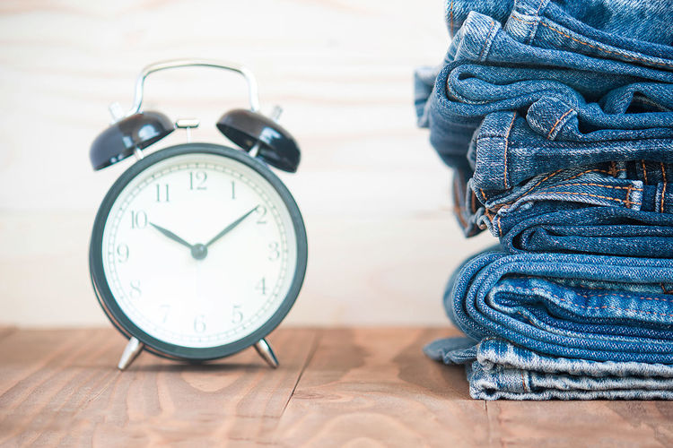 Close-up of alarm clock by stacked jeans on table