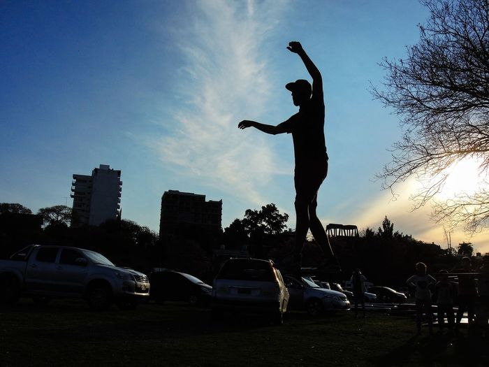 A boy doing slackline in sunset Architecture Argentina Building Exterior Built Structure Car City City Life Cloud - Sky Day In Front Of Land Vehicle Mode Of Transport Nikon Outdoors Parking Silhouette Sky Stationary Statue Street Streetphotography Sunset Transportation Tree Trunk Young Adult