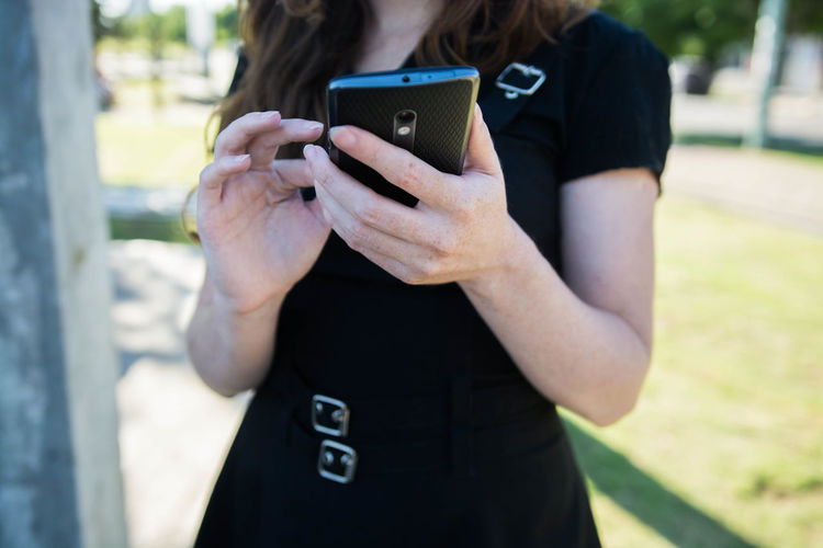 Young woman using a smartphone outdoors in a sunny day One Person Wireless Technology Technology Communication Outdoors Photography Themes Connection Using Phone Front View Focus On Foreground Real People Portable Information Device Smart Phone Day Leisure Activity Standing Midsection Mobile Phone Holding Telephone Hairstyle Young Adult Woman Black Dress Beautiful Spontaneous Candid Sunny Female Portrait Holding Phone