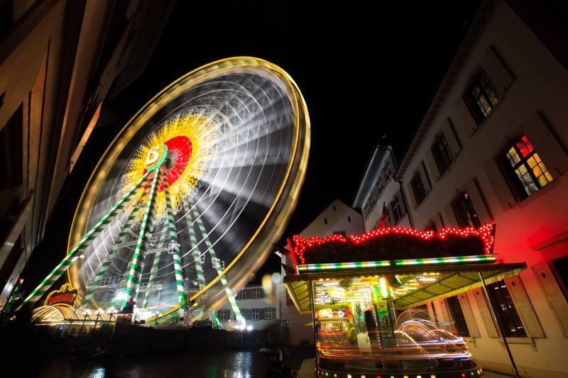 Low angle view of illuminated ferris wheel against sky at night