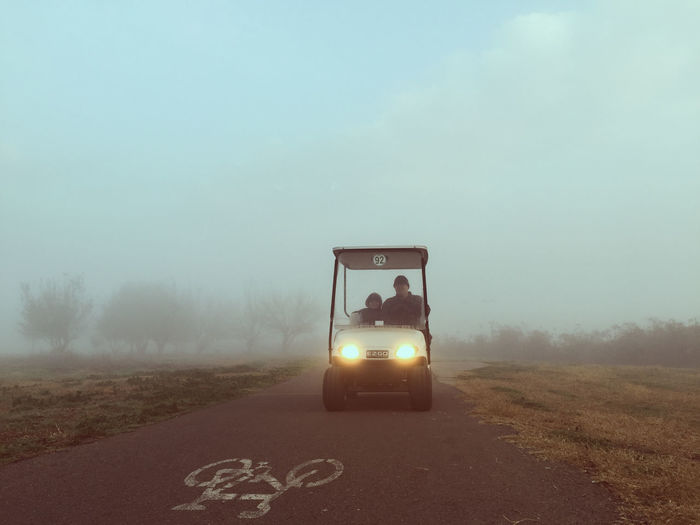 Father With Son In Golf Cart On Road Amidst Field During Foggy Weather