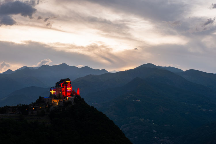 Scenic view of illuminated church on mountain range against sky during sunset