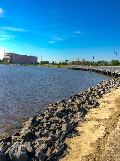 Walking along the waterways of Lake Charles, LA Copy Space Lake Charles Louisiana Architecture Beach Beauty In Nature Blue Building Exterior Built Structure Cloud - Sky Day Groyne Land Nature No People Outdoors Pebble Rock Scenics - Nature Sea Sky Sunlight Tranquil Scene Tranquility Water