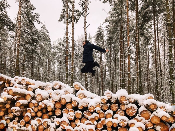 Man jumping on snow covered landscape