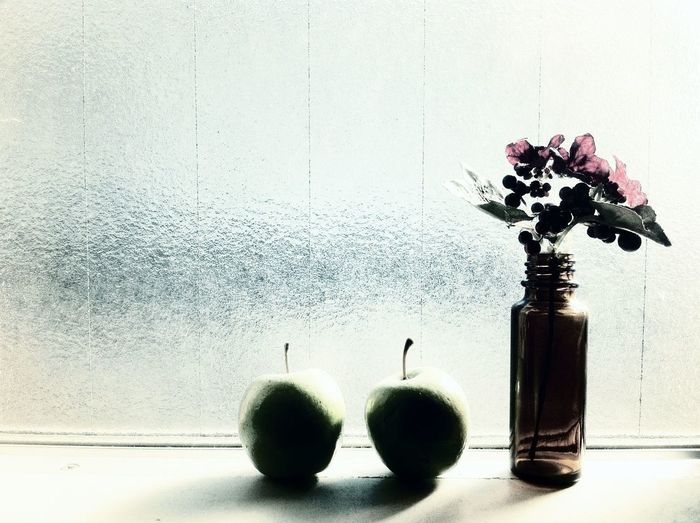 Close-up of flower vase with granny smith apples on window sill