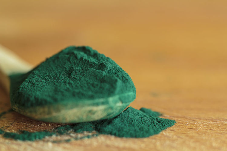 Spirulina algae powder in a wooden spoon
