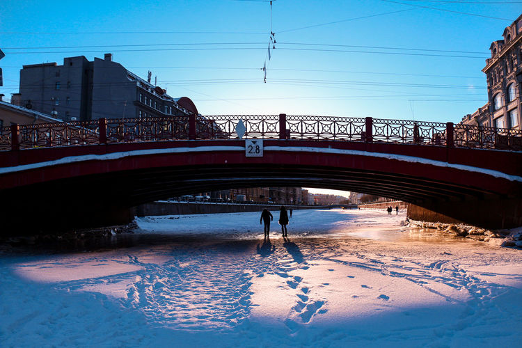 Bridge over river in city against clear sky during winter