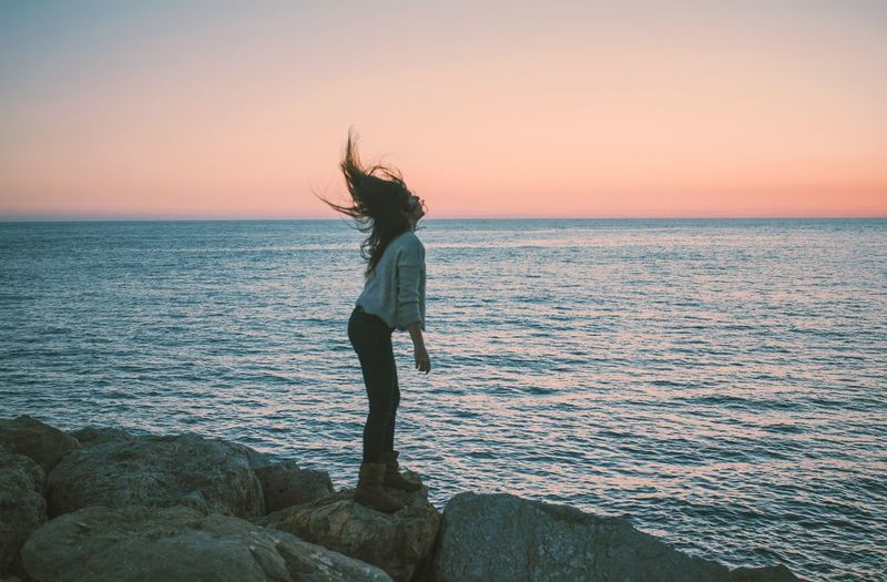 Woman standing on rock by sea against sky during sunset