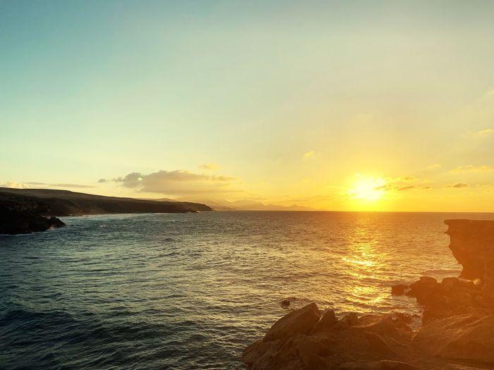 Water Sky Sunset Sea Beauty In Nature Scenics - Nature Tranquility Tranquil Scene Land Sunlight Idyllic Beach Nature Orange Color No People Sun Outdoors Horizon Horizon Over Water