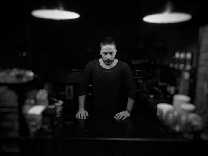 Portrait of man standing at bar counter