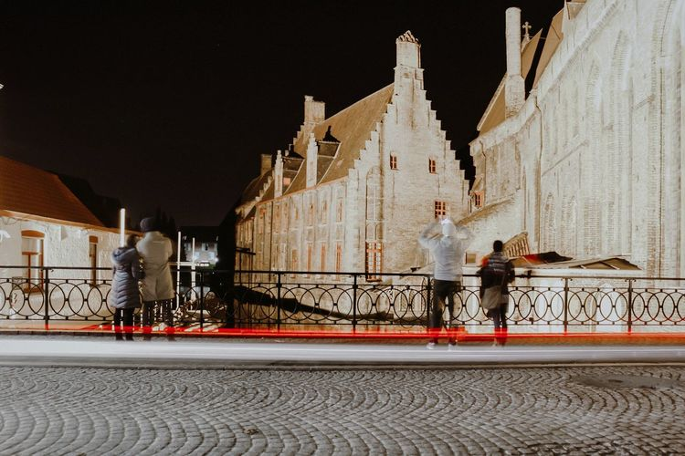 People walking on street amidst buildings in city at night