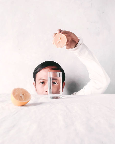 Portrait of man holding lemon over glass of water on table