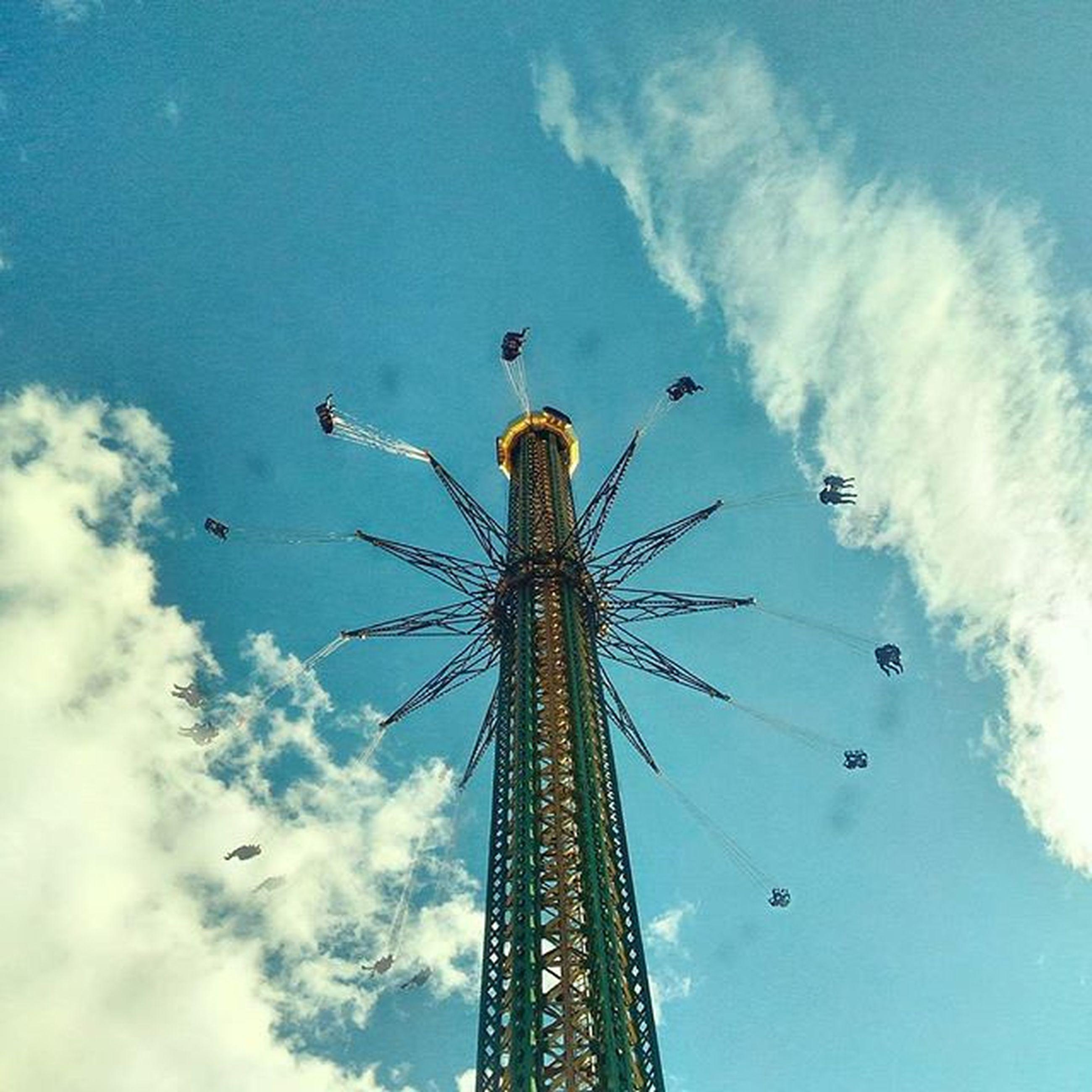low angle view, amusement park, amusement park ride, arts culture and entertainment, sky, ferris wheel, cloud - sky, chain swing ride, fun, enjoyment, built structure, cloudy, tall - high, cloud, architecture, leisure activity, fairground ride, traveling carnival, outdoors, blue