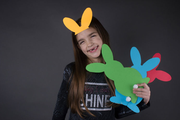 Portrait of smiling girl with eater bunny and pom pom in basket against gray background