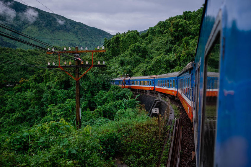 On board of the Reunification Express. Vietnam Bridge - Man Made Structure Cloud - Sky Day Green Color Journey Mode Of Transportation Mountain Nature No People on the move Outdoors Passenger Train Plant Public Transportation Rail Transportation Scenics - Nature Sky Track Train Train - Vehicle Transportation Travel Tree