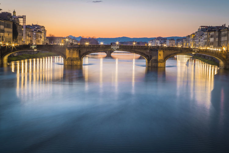 Illuminated Arch Bridge Over River During Sunset