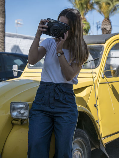 Midsection of woman photographing car