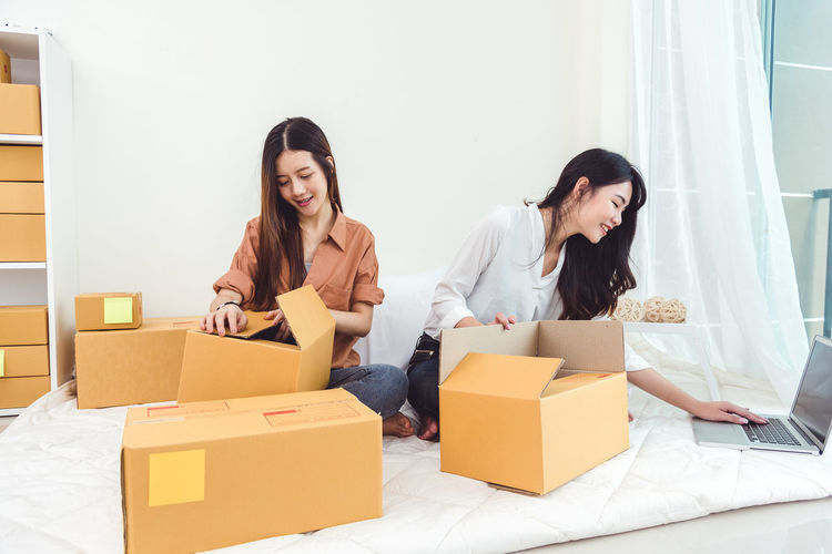 Young Asian woman startup small business entrepreneur SME distribution warehouse with parcel mail box. Owner home office concept. Online marketing and product packaging and delivery service. Shopping Adult Box Box - Container Cardboard Cardboard Box Casual Clothing Deliver Domestic Room Emotion Front View Full Length Happiness Indoors  Lifestyles Moving House Packing Sitting Smiling Togetherness Two People Unpacking Women Young Adult Young Women