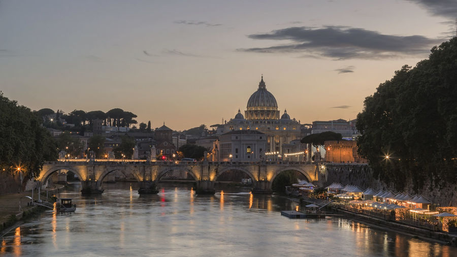 Ponte sant angelo over tiber river in city during sunset