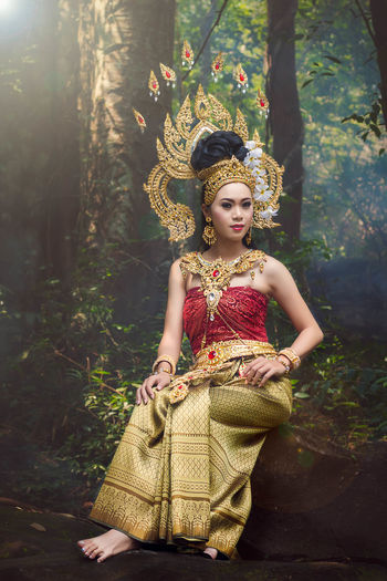 Portrait of beautiful young woman in apsara costume sitting in forest