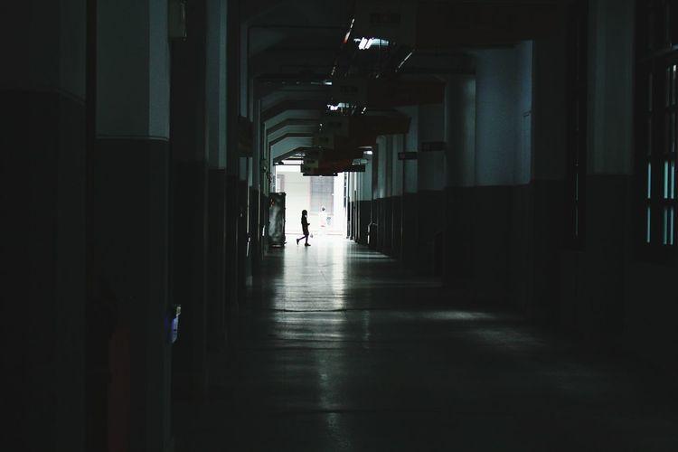 Person Walking In Corridor Of Building