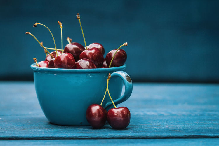 Apple - Fruit Blue Bowl Cherry Close-up Container Focus On Foreground Food Food And Drink Freshness Fruit Group Of Objects Healthy Eating Indoors  No People Red Ripe Selective Focus Still Life Table Wellbeing