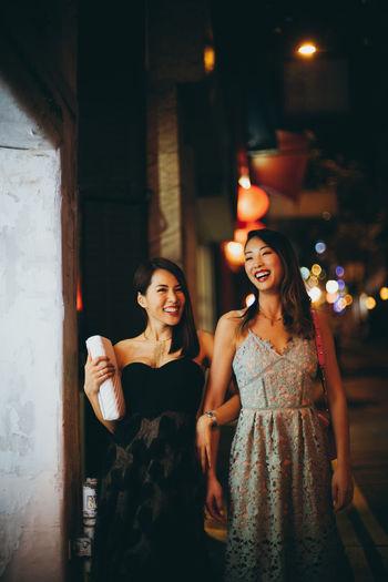 Portrait of friends standing at illuminated night