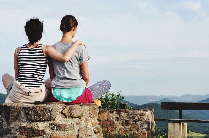 Lesbian couple sitting on wall against sky