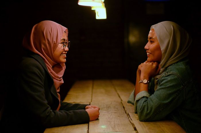 Side view of smiling women in headscarf talking on table