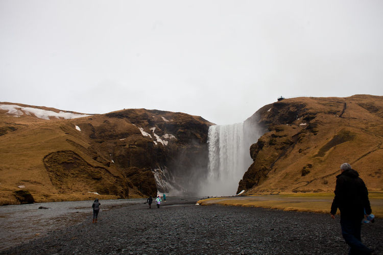 People Visiting Skogafoss Against Sky