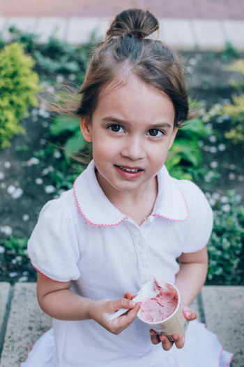 Portrait of girl holding ice cream while sitting outdoors