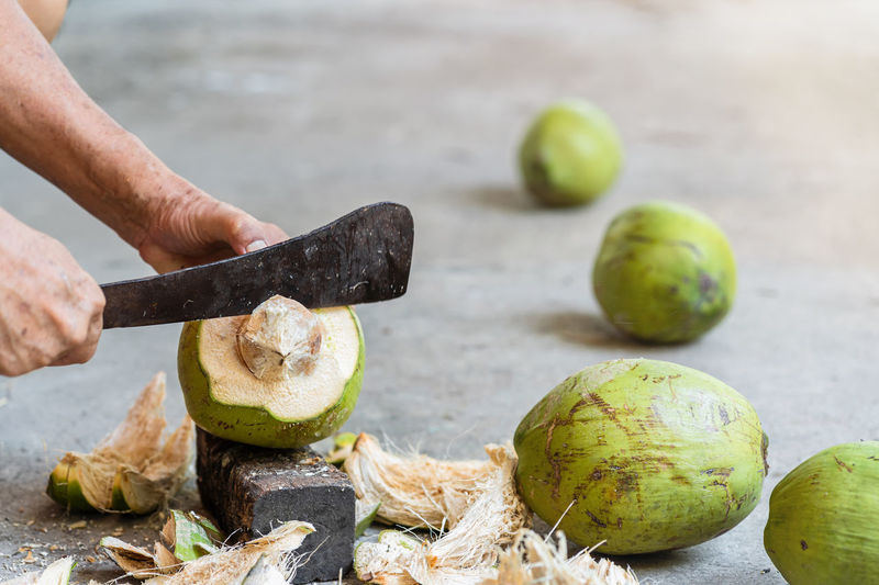 Midsection of man cutting coconut