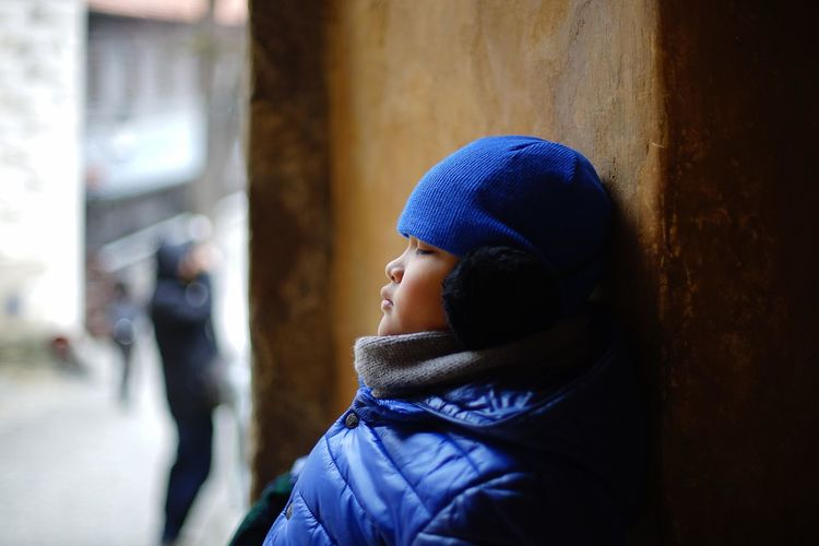 Profile view of boy wearing warm clothing while leaning on wall