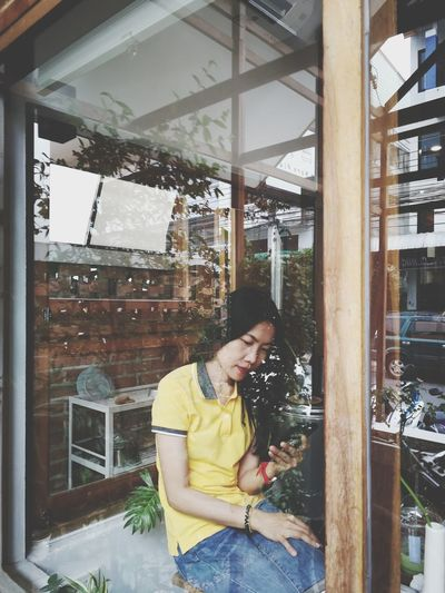 Woman using mobile phone in cafe seen through window