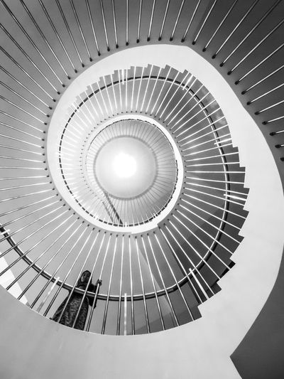 Low Angle View Of Woman Walking On Spiral Staircase