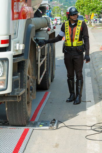 Police set up portable wheel load scales for determining the weight of heavy vehicles on the road for law enforcement and could reduce roads accidents . Adult Cap Commercial Land Vehicle Day Full Length Hardhat  Headwear Helmet Land Vehicle Law Enforcement Men Occupation One Person Outdoors People Portable Wheel Load Scales Protective Workwear Real People Reflective Clothing Standing Transportation Uniform Working