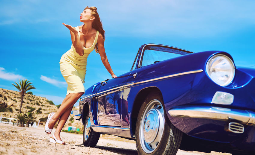 Attractive woman near retro car blowing a kiss Attractive Beautiful Woman Blond Blowing Kisses Cabriolet Car Caucasian Convertible Car Happiness Happy Lady One Person Outdoors Pose Retro Car Retro Styled Sixties Slim Smile Summer Summertime Sunny Day Vintage Cars Woman Young Adult