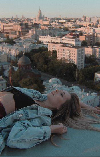 High angle view of woman lying on terrace against cityscape