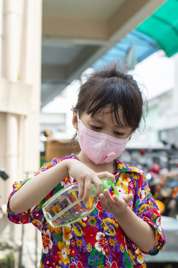 Cute girl wearing mask using hand sanitizer outdoors