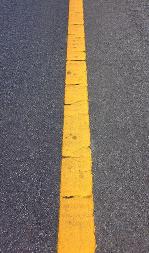 High angle view of yellow arrow symbol on road in city