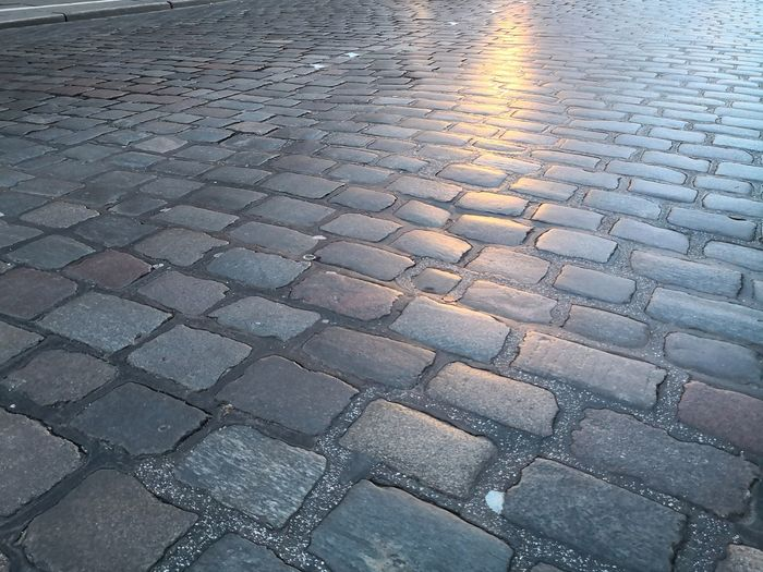 Cobblestone street background pavement with light reflection Copy Space Evening Cooblestone Cobbled Streets Cobblestone Streets Backgrounds Full Frame Pattern Stone Tile Cobblestone Textured  Paving Stone Cobbled Rough Rugged Surface Geometry Uneven Single Lane Road Geometric Shape Circular Square Shape Rectangle Seamless Pattern Skylight Clear Tiled Floor Stone Material Romantic