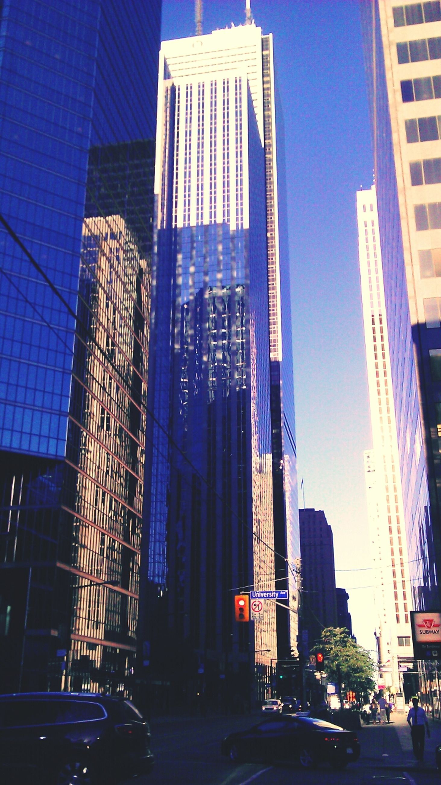building exterior, architecture, built structure, city, skyscraper, modern, office building, tall - high, illuminated, low angle view, building, blue, tower, city life, car, clear sky, street, night, financial district, transportation