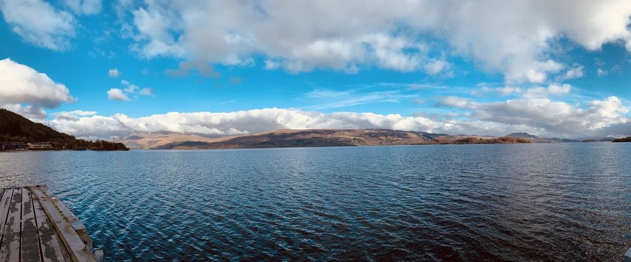 Panoramic view of lake and mountain in Scotland. Absence Beauty In Nature Blue Sky And Clouds Calm Copy Space Day Escape Freedom Getting Away From It All Hill Reflections In The Water Non-urban Scene Rippled Scenics - Nature Tranquility No People Blue Lake Sunlight Scottish Scotland Purity Scottish Highlands Remote Landscape