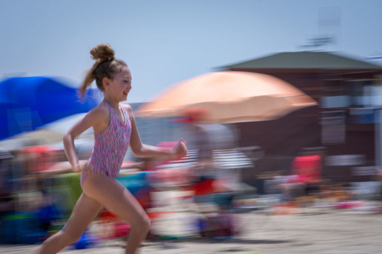 Side View Of Girl Running At Beach During Summer